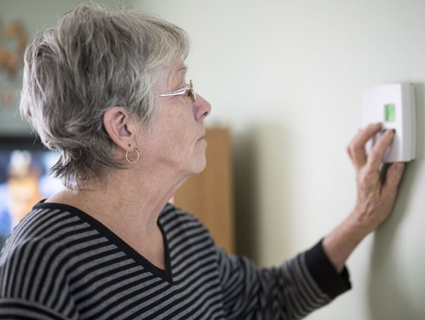 Elderly lady changing thermostat