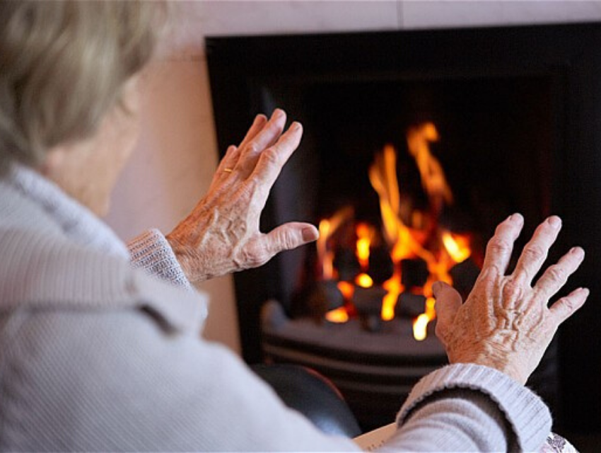 Elderly lady warming hands by fire