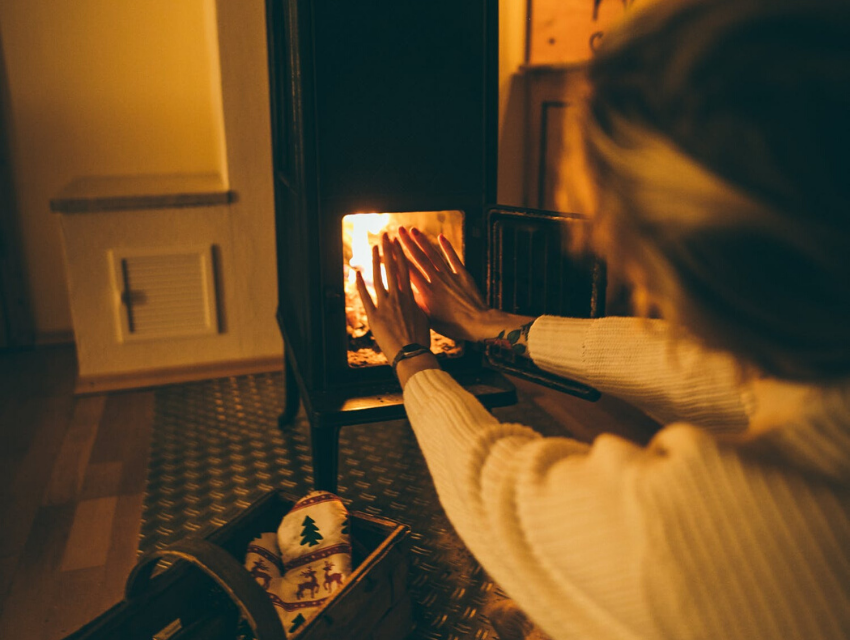 Lady warming hands by fire